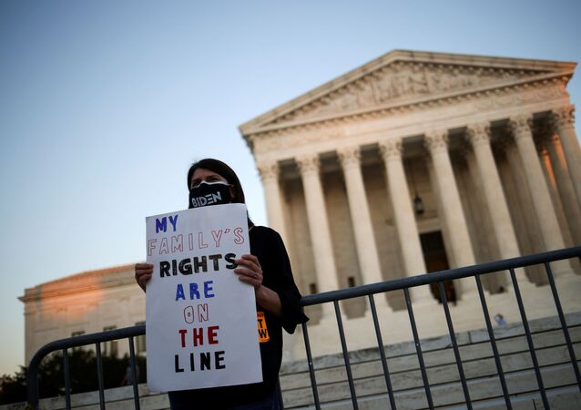 A person wearing a protective face mask reading Biden holds a placard in front of the U.S Supreme Court building, in Washington D.C., U.S., October 21, 2020.