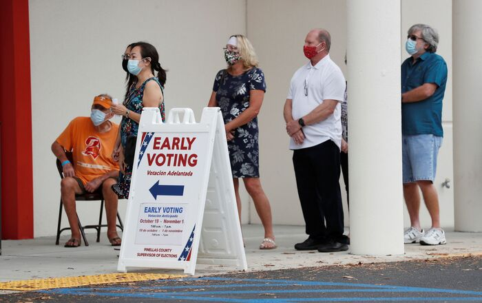 People line up at the Supervisor of Elections Office polling station as early voting begins in Pinellas County ahead of the election in Largo, Florida, US, 21 October 2020