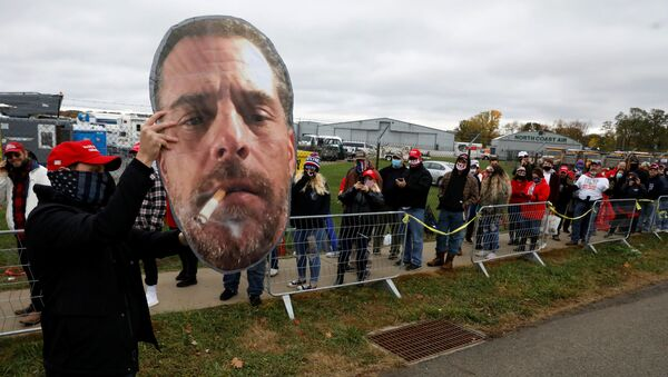 A supporter of U.S. President Donald Trump holds up a photo of Hunter Biden for fellow supporters as they wait in line to attend Trump's campaign event at Erie International Airport in Erie, Pennsylvania, U.S. October 20, 2020. - Sputnik International