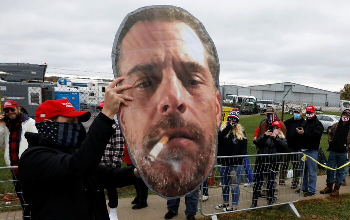 A supporter of U.S. President Donald Trump holds up a photo of Hunter Biden for fellow supporters as they wait in line to attend Trump's campaign event at Erie International Airport in Erie, Pennsylvania, U.S. October 20, 2020.