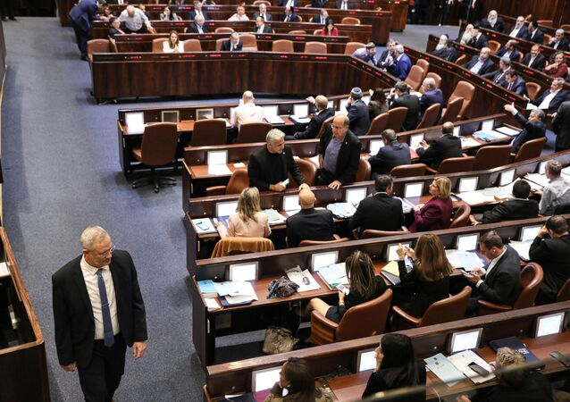 Israeli Kahol Lavan (Blue and White) political alliance leader Benny Gantz (L) walks during a session of the Knesset (Israeli parliament) in Jerusalem on December 11, 2019.