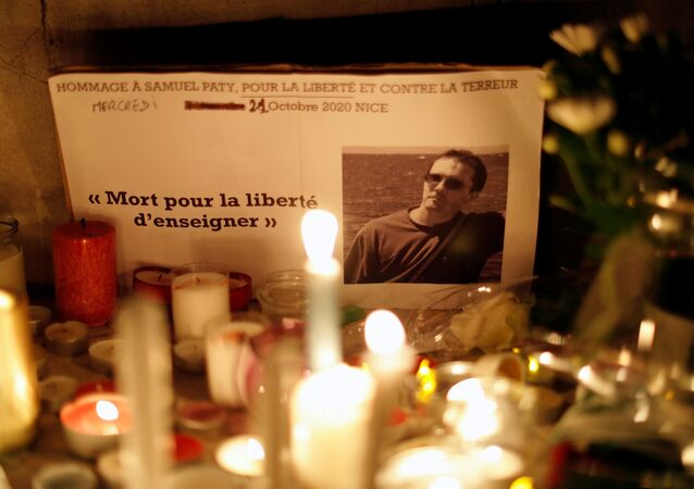 Candles are lit at a makeshift memorial as people gather to pay homage to Samuel Paty, the French teacher who was beheaded on the streets of the Paris suburb of Conflans-Sainte-Honorine, as part of a national tribute, in Nice, France, October 21, 2020