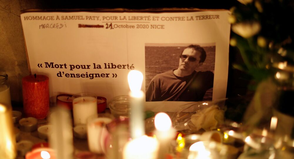 Candles are lit at a makeshift memorial on 21 October 2020 in Nice, France, as part of a national tribute to Samuel Paty, the French history teacher who was beheaded on the streets of the Paris suburb of Conflans-Sainte-Honorine.