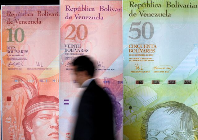 A man walks past big samples of Venezuelan banknotes at the Central Bank headquarters in Caracas August 22, 2013.