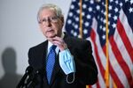 Senate Majority Leader Mitch McConnell (R-KY) holds a face mask while participating in a news conference at the U.S. Capitol in Washington, U.S., October 20, 2020.
