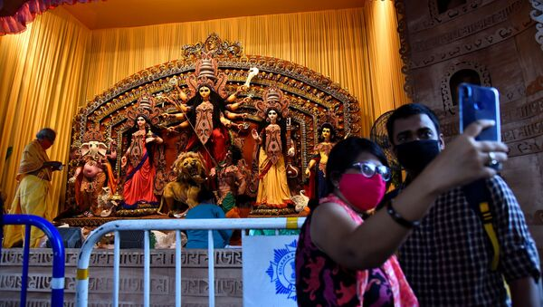 Hindu devotees take a selfie in front of an idol of Hindu goddess Durga before prayer at a cordoned off pandal or temporary platform, on the first day of Durga Puja festival, amidst the spread of COVID-19 in Kolkata, India, October 22, 2020 - Sputnik International