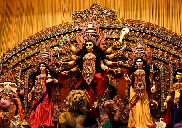 Hindu devotees take a selfie in front of an idol of Hindu goddess Durga before prayer at a cordoned off pandal or temporary platform, on the first day of Durga Puja festival, amidst the spread of COVID-19 in Kolkata, India, October 22, 2020
