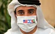 A picture taken on August 31, 2020, shows an Emirati man, wearing a protective mask with the flags of the US, Israel and the UAE, ahead of the arrival of the first commercial flight from Israel, carrying a US-Israeli delegation to the UAE following a normalisation accord, at the Abu Dhabi airport