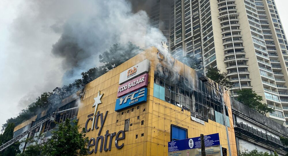 Firefighters (L) douse a fire at a City Centre shopping mall in Mumbai on October 23, 2020