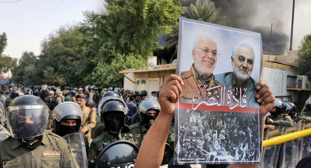 A supporter of Hashid Shaabi (Popular Mobilization Forces) holds a picture of late Iran's Quds Force top commander Qassem Soleimani and Iraqi militia commander Abu Mahdi al-Muhandis who were killed in a U.S. airstrike during a protest in Baghdad, Iraq October 17, 2020