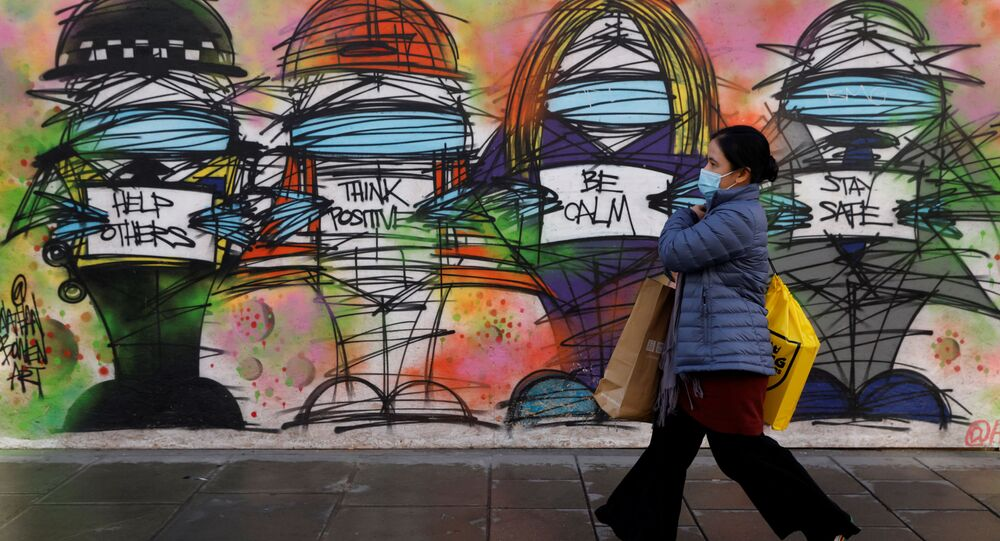 A woman wearing a face mask walks past graffiti, amid the coronavirus disease (COVID-19) outbreak, in central London Britain October 15, 2020