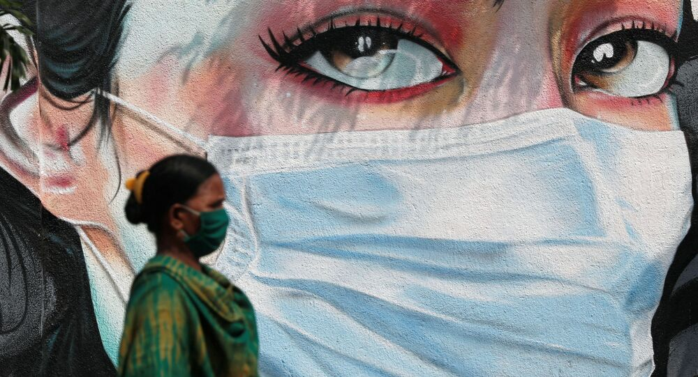 A woman walks past a graffiti of a girl wearing a protective mask amidst the spread of the coronavirus disease (COVID-19) in Mumbai, India, October 23, 2020