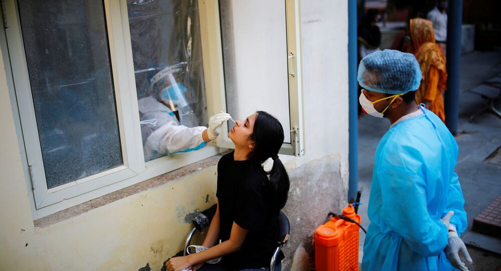A health worker in personal protective equipment (PPE) collects a sample using a swab from a person at a local health centre to conduct tests for the coronavirus disease (COVID-19), amid the spread of the disease, in New Delhi, India October 7, 2020
