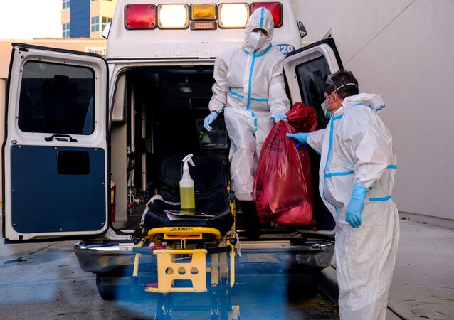 EMTs cleanse their materials outside Memorial West Hospital where coronavirus disease (COVID-19) patients are treated, in Pembroke Pines, Florida, U.S. July 13, 2020.