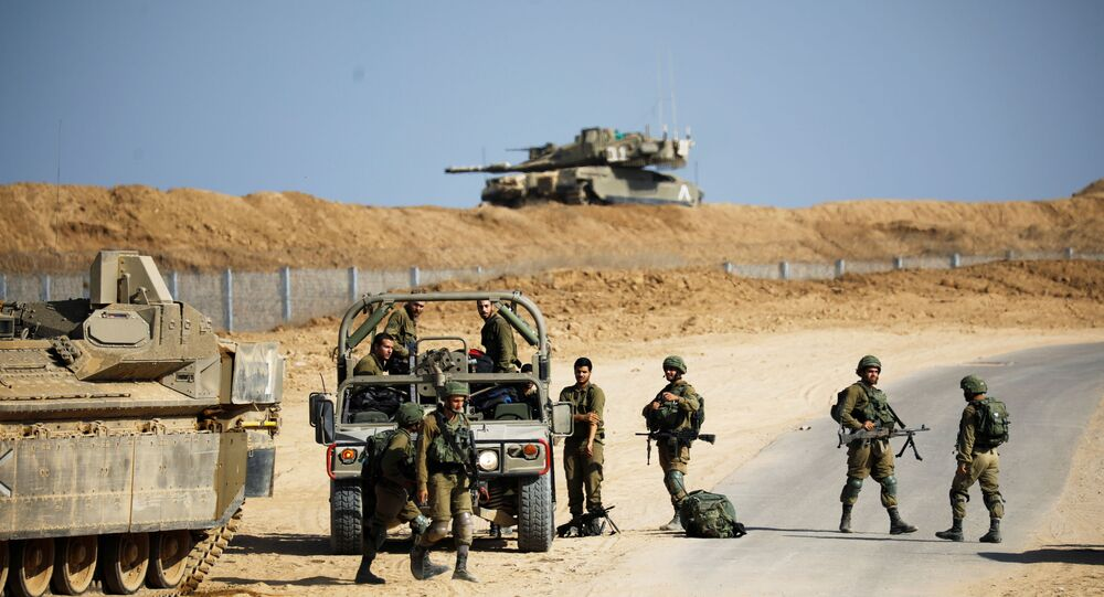 Israeli soldiers stand near a military jeep and an armoured personnel carrier (APC) close to the site where Israel discovered a new cross-border tunnel from the Gaza Strip that its military said extended dozens of metres underground and into southern Israel, along the border with the Gaza Strip, southern Israel October 21, 2020. REUTERS/Amir Cohen