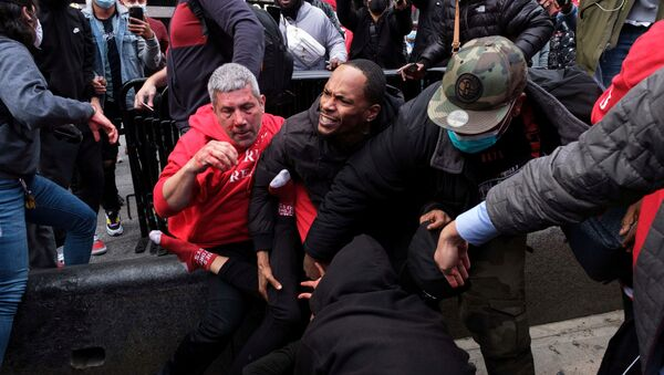 A man protects a supporter of U.S. President Donald Trump from anti-Trump protesters after clashes in the Manhattan borough of New York City, U.S. October 25, 2020. - Sputnik International