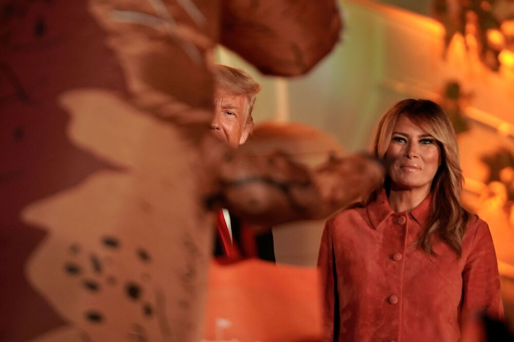 US President Donald Trump and first lady Melania watch as a guest dressed as a dinosaur walks at their Halloween event at the White House on 25 October 2020.