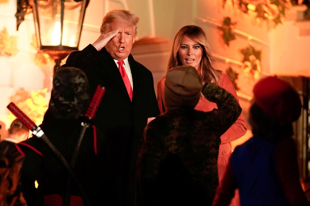 US President Donald Trump salutes children in costume as he and first lady Melania Trump host a Halloween event at the White House on 25 October 2020.
