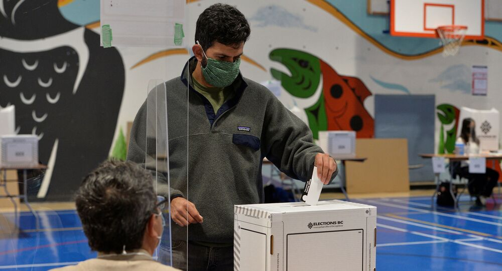 A voter casts a ballot during the B.C. provincial election in Vancouver, British Columbia, Canada October 24, 2020.