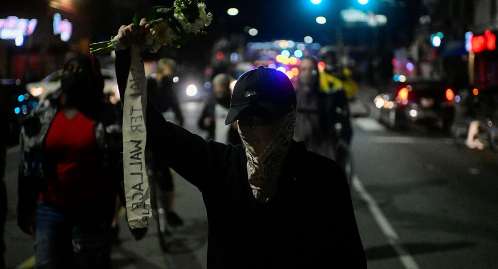 A demonstrator holds a bouquet of flowers during a rally after the death of Walter Wallace Jr., a Black man who was shot by police in Philadelphia, Pennsylvania, U.S., October 27, 2020.