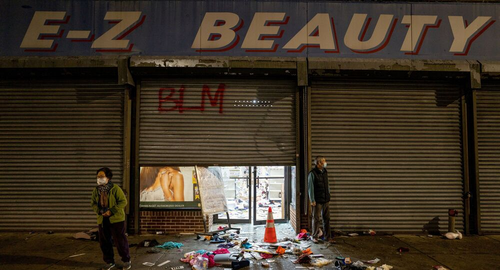 A business owner stands outside of her looted beauty supply store following protests over the police shooting death of Walter Wallace in Philadelphia, Pennsylvania, U.S., October 27, 2020.