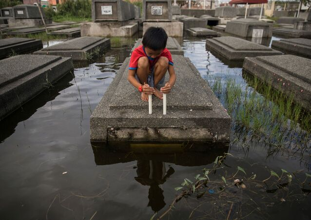 A boy attempts to keep a candle lit in a flooded cemetery following Typhoon Molave, in Masantol, Pampanga, Philippines, October 27, 2020