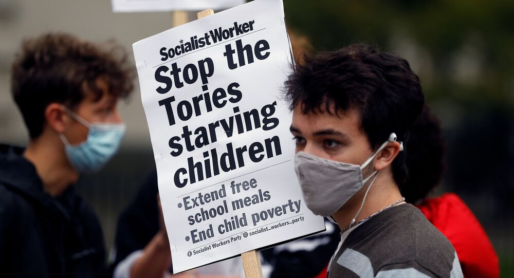 A boy holds a banner during a protest demanding free school meals for children in England