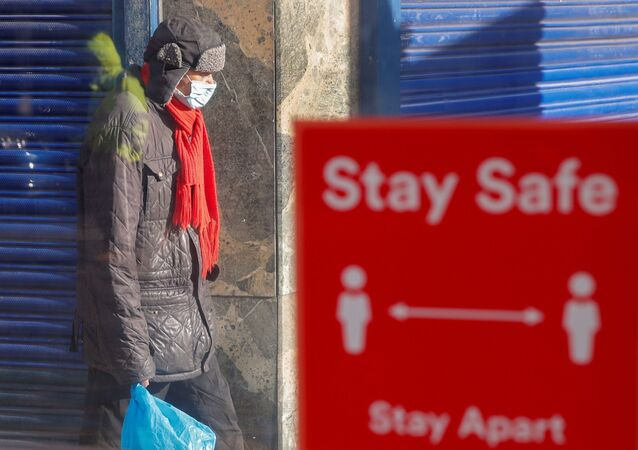 A person wearing a protective mask walks near a social distancing sign, amid the outbreak of the coronavirus disease (COVID-19), in Coventry, Britain, 25 October 2020.