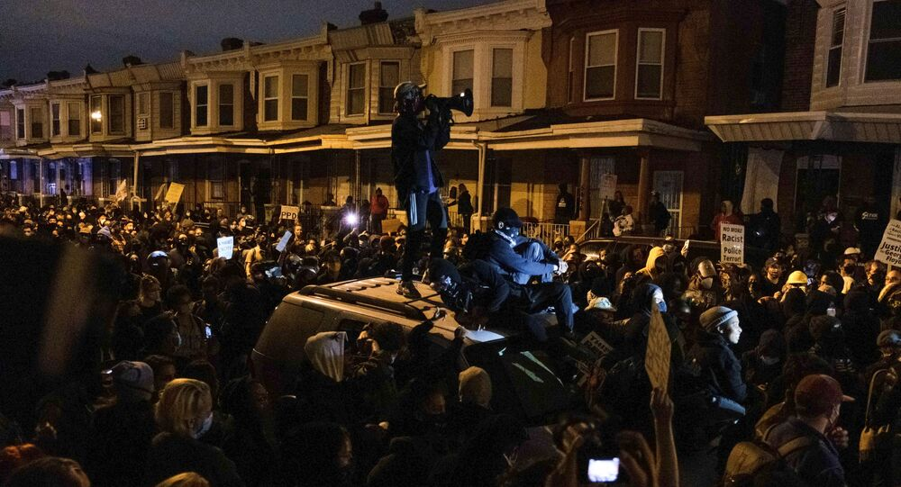 A protester stands on a vehicle as demonstrators clash with riot police during a rally after the death of Walter Wallace Jr., a black man who was shot by police in Philadelphia, Pennsylvania, 27 October 2020.