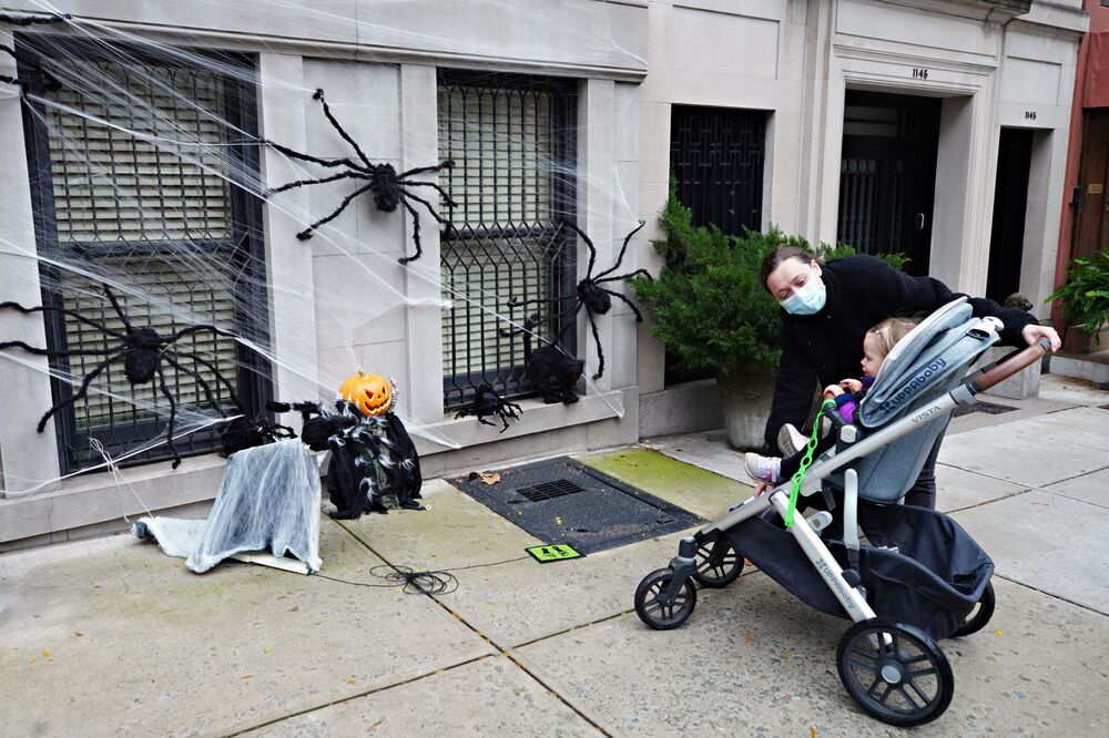 A woman shows Halloween decorations to a child, New York City, 28 October 2020.
