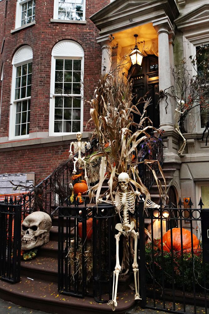 Skeletons, pumpkins are placed outside a home in New York City to decorate the area for Halloween.