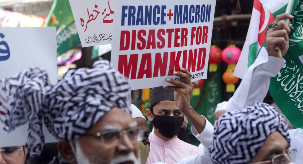 People hold placards and shout slogans during a protest against the publications of a cartoon of Prophet Mohammad in France and Macron's comments, in Mumbai, India, October 28, 2020