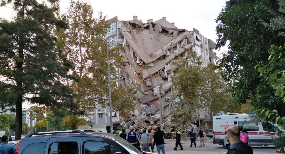 Locals look at a damaged building after a strong earthquake struck the Aegean Sea on Friday and was felt in both Greece and Turkey, where some buildings collapsed in the coastal province of Izmir, Turkey, October 30, 2020