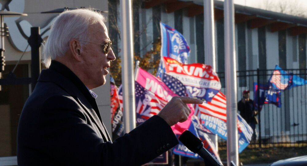 Democratic U.S. presidential nominee and former Vice President Joe Biden speaks as supporters of U.S. President Donald Trump hold up flags and posters nearby, during a drive-in campaign stop in St. Paul, Minnesota, U.S., October 30, 2020.