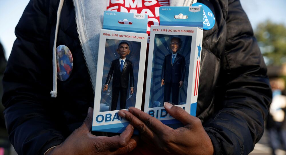 A person holds real life action figures depicting democratic U.S. presidential nominee and former Vice President Joe Biden and former U.S. President Barack Obama during a campaign canvas kickoff in Bloomfield Hills, Michigan, U.S., October 31, 2020.