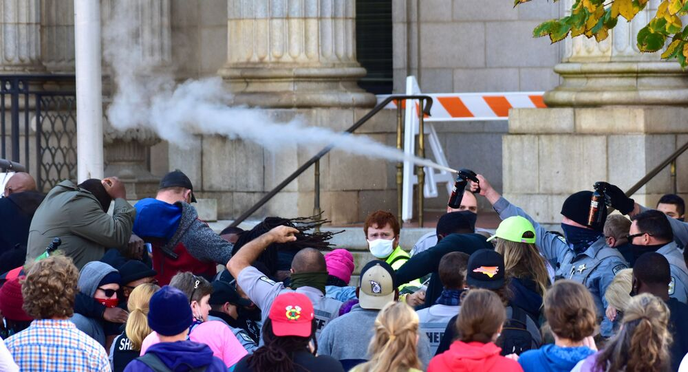 Law enforcement officers spray protesters shortly after a moment of silence during a Get Out The Vote march in Graham, North Carolina, U.S. October 31, 2020.