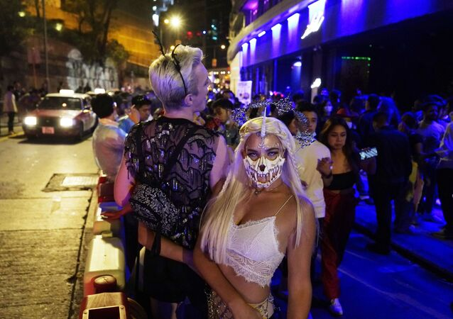 People wearing costumes and face masks to protect against the coronavirus, celebrate Halloween in Central of Hong Kong, early Sunday, Nov. 1, 2020.