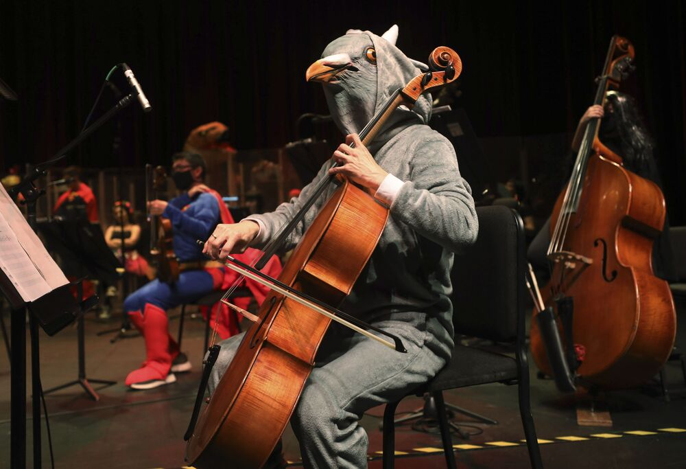 A violoncellist in a bird costume participates in a recorded Halloween concert by the Bogota and Youth Philharmonic Orchestras at the Colsubsidio Theatre in Bogota, Colombia, Friday, 30 October 2020. Due to the COVID-19 pandemic, this year's annual Halloween concert is being recorded without a live audience and will be broadcast on television the following day.