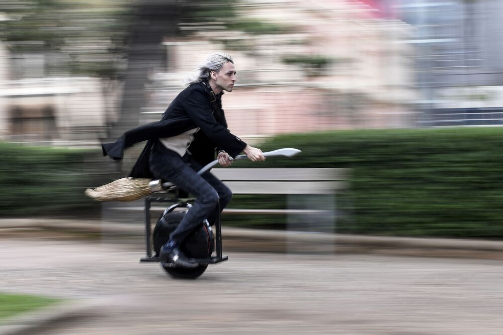 Alessandro Russo rides his flying broom on Halloween at Praca da Liberdade Square, in Belo Horizonte, Brazil, on 31 October 2020. - Russo developed a broom inspired by Harry Potter and the model is coupled to an electric unicycle and it is possible to run it at a speed of up to 60 km/h.