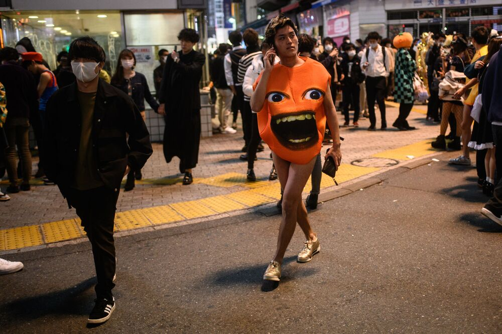 A reveller (C) in a costume walks in the Shibuya district in Tokyo during Halloween on 31 October 2020.