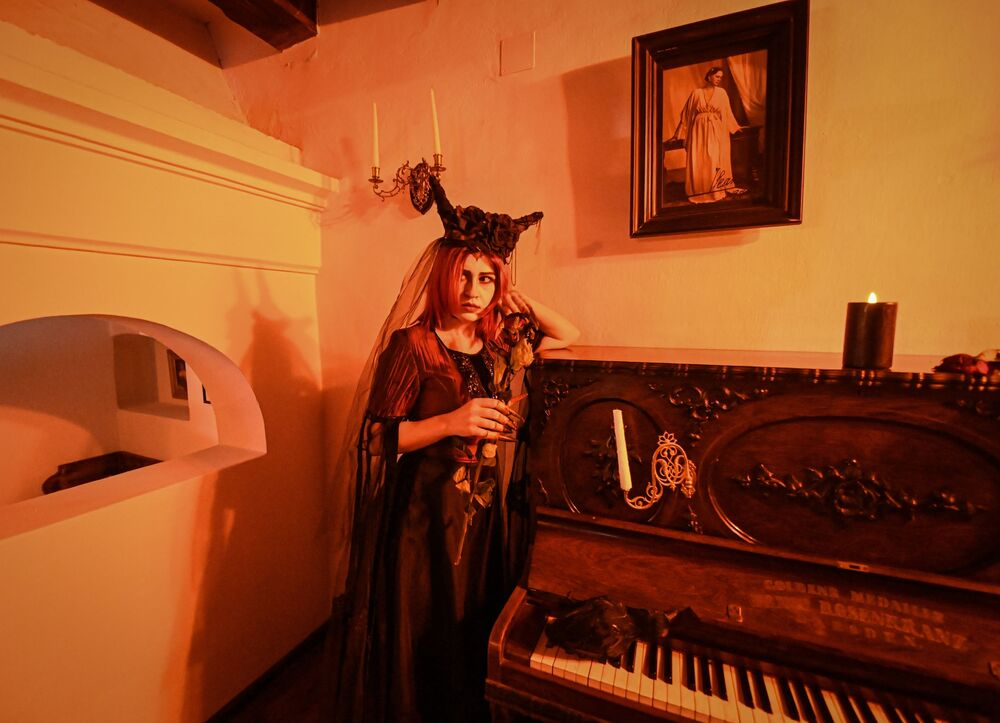 An actress dressed as the wife of the character Dracula poses during a special tour at Bran Castle, organised for Halloween in Bran village 31 October 2020. - Bran Castle is apparently the only castle in Romania's historical region of Transylvania that actually fits Bram Stoker's description of Dracula's Castle; it is known throughout the world as Dracula's Castle.