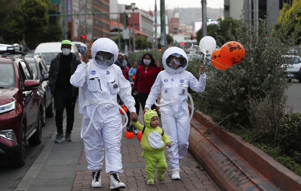 People wearing NASA astronaut costumes trick-or-treat with a child dressed as an alien on Halloween in La Paz, Bolivia, Saturday, 31 October 2020, amid the COVID-19 pandemic.
