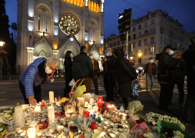 A woman lights a candle outside Notre-Dame de l'Assomption Basilica in Nice on October 31, 2020, to pay tribute to the victims two days after a knife attacker killed three people, cutting the throat of two, inside the church of the French Riviera city, and police arrest a young Tunisian migrant from Sfax who arrived in Europe only last month, according to French prosecutors. (Photo by Valery HACHE / AFP)