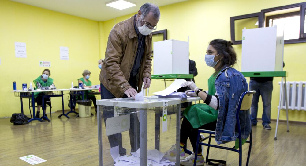 A man wearing a face mask to help curb the spread of the coronavirus, casts his ballot at a polling station during the parliamentary elections in Tbilisi, Georgia, Saturday, Oct. 31, 2020. The hotly contested election between the Georgian Dream party, created by billionaire Bidzina Ivanishvili who made his fortune in Russia and has held a strong majority in parliament for eight years, and an alliance around the country's ex-President Mikheil Saakashvili, who is in self-imposed exile in Ukraine.
