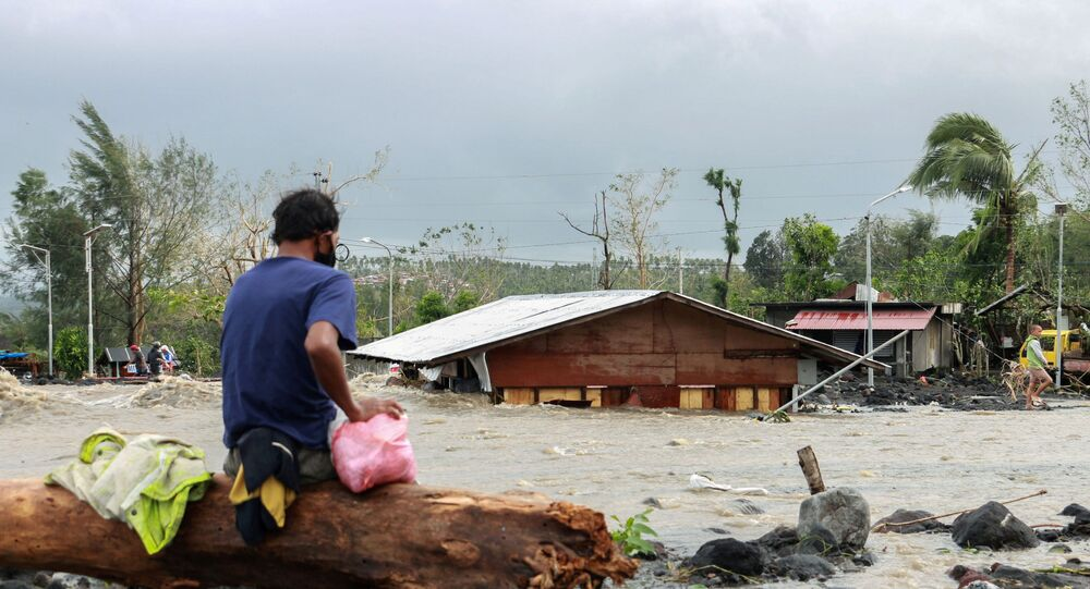 A man looks at his house buried under the pile of rubble and sand following flash floods brought by Typhoon 'Goni' in Barangay Busay, Daraga town, Albay province, Philippines, November 1, 2020.