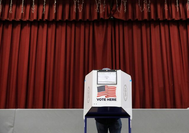 A person fills out a ballot in a privacy booth at a polling station located in the Monsignor John D. Burke Memorial Gym at the Church of the Holy Child in Staten Island, during early voting in New York City, U.S., October 25, 2020.