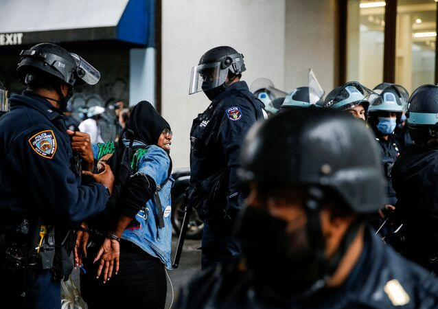 A woman is detained while Black Lives Matter members and people confront NYPD during a march against far right movement and Trump administration in the Manhattan borough of New York City, U.S. November 1, 2020.