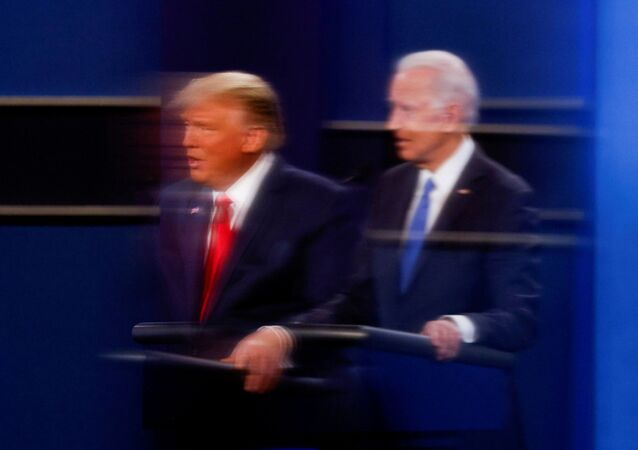 FILE PHOTO: U.S. President Donald Trump and Democratic presidential nominee Joe Biden are reflected in the plexiglass protecting a tv camera operator from covid as they participate in their second 2020 presidential campaign debate at Belmont University in Nashville, Tennessee, 22 October 2020