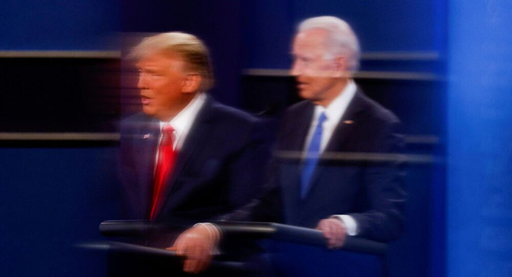 FILE PHOTO: U.S. President Donald Trump and Democratic presidential nominee Joe Biden are reflected in the plexiglass protecting a tv camera operator from covid as they participate in their second 2020 presidential campaign debate at Belmont University in Nashville, Tennessee, U.S., October 22, 2020