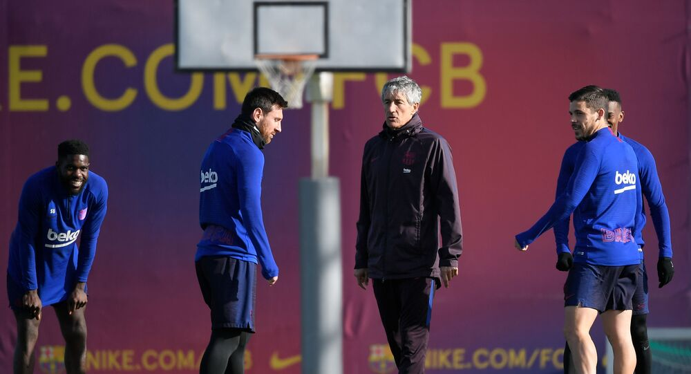 Barcelona's new coach, Spaniard Quique Setien (3L), talks with Barcelona's Argentine forward Lionel Messi (2L) during a training session at the Joan Gamper Sports City training ground in Sant Joan Despi on January 18, 2020